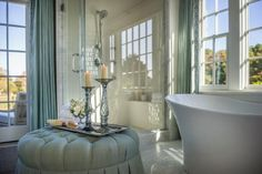 A plush tufted ottoman holds romantic accessories and adds a feminine touch to this incredible master bathroom.
