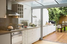 The kitchen continues out into the garden with a clever glass partition, making the room more spacious as it blurs the lines between indoors and outdoors. #Balcony #Barbecue #CleverKitchenSolution #Gardenflooring #GardenFurniture #GlassExtention #GlassPartition #GlassRoof #GlassSeparation #Glasswall #Grill #Jieldé #KitchenCounter #KitchenFan #KitchenSolution #Lantern #OpenSpace #OutdoorCooking #OutdoorIndoors  #OutdoorSeating #OutsideKitchen #Terrace
