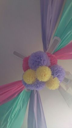 Tent inspired ceiling - multi coloured table covers draped across ceiling with tissue paper pom pom chandelier centre piece perfect room transformer @The Party Cupboard
