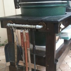Homemade table for big green egg- bottle opener and rack for grilling tools.