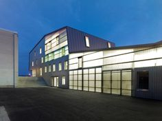 gathered under one, long undulating roof, this multipurpose building in gland, switzerland by swiss firm bunq architectes consists of halls, warehouses, garages, township offices and local companies rooms.