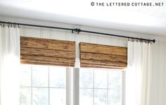 Hang curtains and/or blinds *above* the windows to give the illusion of larger windows and let in more light.