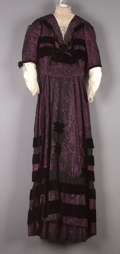 Dress Designer: Mme.J. Baer Date: 1905 Media: Silk Brocade, Georgette, Lace, Velvet, Taffeta Country: United States Accession Number: 54791a-b Dress of figured silk taffeta in floral scroll design and cream bobbin lace: V necked bodice, lower sleeves of cream bobbin lace; with ankle length skirt trimmed with horizontal bands of velvet and taffeta; taffeta petticoat.