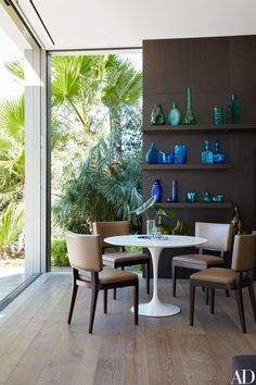 Vintage Blenko glass brightens the den. Eero Saarinen table by Knoll; Christian Liaigre chairs.
