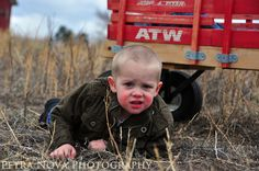 Adorable photography pose for child / boy in field with red wagon