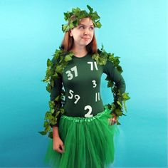 A woman dressed in green wearing leaves and a shirt with prime numbers on it.