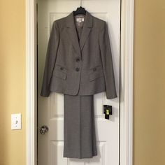 Gray LeSuit Pantsuit. NWT. Size 12. This gray LeSuit Pantsuit has attractive double-pocket detailing in front of jacket and light padding in the shoulders. The fabric has the look of more expensive gray suiting wool, although it is constructed of polyester. The straight-leg, flat-front pants have a 31 in inseam. Le Suit Other