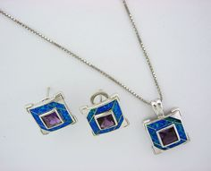 925 Sterling Silver and Blue Opal Pendant has 20-inch long sterling silver chain, and the pendant has match earrings. This beautiful pendant has square shape, and in the middle, there is a purple amethyst. This necklace weights 19 gram.
