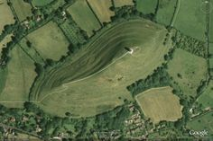 Glastonbury Tor: Aerial View-- Until two thousand years ago, the sea washed right to the foot of the Tor, nearly encircling the cluster of hills. The sea was gradually succeeded by a vast lake. Although a peninsula, the Tor would have looked like an island from most angles of approach: an old Celtic name for Glastonbury is Ynys-witrin, the Island of Glass.  Excavations on the Tor have revealed Neolithic flint tools and Roman artifacts, indicating some use of the Tor since very ancie
