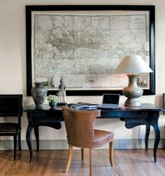 Map of London in black frame over beautiful black table desk flanked by black chairs, with stone colored accessories and brown leather chair.