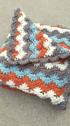 I just finished this baby blanket for a coworker who is doing grey walls with burnt orange and cream accents in their nursery. Love this pattern and have made several blankets from it.