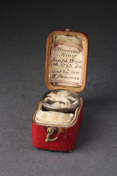 An Interesting Cravat or Scarf Ring once belonging to the artist Joseph Wright  (1734 – 1794) known as 'Wright of Derby'  The silver ring with a finely carved ivory relief of Pegasus and Bellerophon against a dark ground. The red leather and wood box with a label to the inner lid reading: 'Memorial ring. Joseph Wright ob 1797. A.262 lent by Mrs W Bemrose'  18th Century   Size: 3cm wide, 2cm deep – 1¼ ins wide, ¾ ins deep