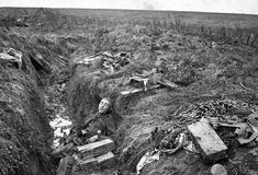 """A German machine gunner lies dead at his post in a trench near Hargicourt, in France on September 19th, 1918. From the original caption: """"He had courageously fought to the last using his gun with deadly effect against the advancing Australian troops."""