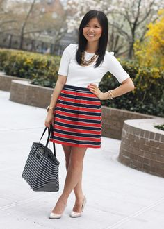 H cream structured shoulder top; J.Crew Factory red and navy striped skirt; Juicy Couture statement necklace; gemstone cuff bracelet; Kate Spade City Sidney Striped tote bag; Pour La Victoire Mai wedge; J.Crew pave square link bracelet
