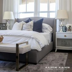 Contemporary bedroom features a charcoal gray wingback bed dressed in navy blue velvet pillows, placed in front of windows dressed in white curtains, flanked by white nightstands and mercury glass lamps.