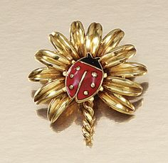 ENAMEL LADYBIRD BROOCH, CARTIER, 1940S.  Designed as a palm leaf applied to the centre with a red and black enamel ladybird, signed Cartier Paris, maker's marks and French assay marks, case by Cartier Paris.