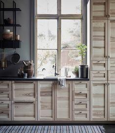 Nouvelle cuisine IKEA TORHAMN Cuisine avec portes et tiroirs en frêne naturel, combinés avec des poignées en fer forgé et des plans de travail à motif minéral noir.