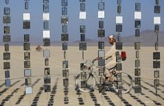 "Austin Cable rides past an art installation during the Burning Man 2015 ""Carnival of Mirrors"" arts and music festival in the Black Rock Desert of Nevada, August 31, 2015. Approximately 70,000 people from all over the world are gathering at the sold-out festival to spend a week in the remote desert to experience art, music and the unique community that develops. REUTERS/Jim Urquhart"