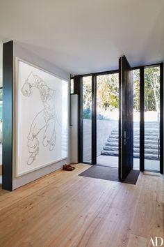 The entryway's custom-made pivot door is by Reilly Windows & Doors   archdigest.com
