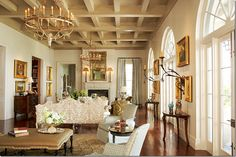 Architect Ken Tate. Note rustic coffered ceiling. Love the swooping sconces. Room by Ann Holden. The grand living room has twin chandeliers and two main seating areas.