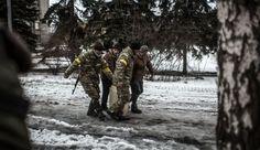 Ukrainian soldiers help civilians carry water in the Ukrainian city of Debaltseve, in the Donetsk.