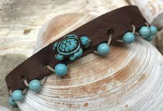 Love this combination! A tan leather strap strung with turquoise beads and a turquoise turtle, secured with a bronze-gun metal button clasp.     This piece is stunning solo or stacked.    Looking for special gift?    If you like the design of this piece, but would like one made from a different color, I would love to help you. Just send me an email or start a conversation.    This item ships in a jewelry box and padded envelope for extra protection.     Please stop by to see all the things…