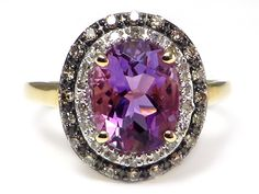 This fab ring has a 9x7 mm (2.21 ct) oval cut, genuine amethyst in the center surrounded by a halo of .25 ctw of brown (also called cognac) and white diamonds! The setting is solid 10k yellow gold. #AmethystBrownDiamondRing #AmethystDiamondRing
