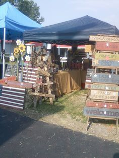 Various handcrafted items and signs displayed at a craft show.