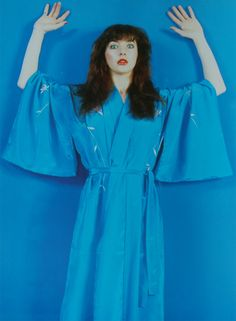Kate Bush blue kimono      [Image description: 1980s-era photo of musician Kate Bush wearing a blue kimono against a blue wall of the same hue. She has her hands raised and a wide-eyed expression.]
