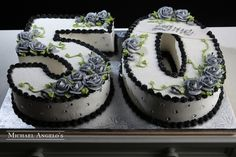 Grey Roses 50 Shaped as the number this cake is iced in buttercream and trimmed in black. The numbers are decorated with grey roses and accented with sparkly gems. 50th Birthday Cake For Women, Number Birthday Cakes, Birthday Sheet Cakes, Number Cakes, Lemon And Coconut Cake, 50th Cake, Cake Flavors, Buttercream Cake, Savoury Cake
