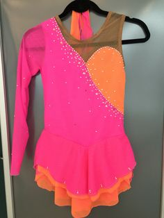 Neon pink and orange figure skating dress with various size size crystals. One sleeve asymmetric by Suzanne skate dresses on face book or sk8dress.com