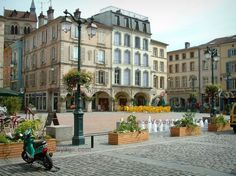 Épinal: Place des Vosges square with plants, flowers, fountains, café terraces and arcaded houses - France-Voyage.com
