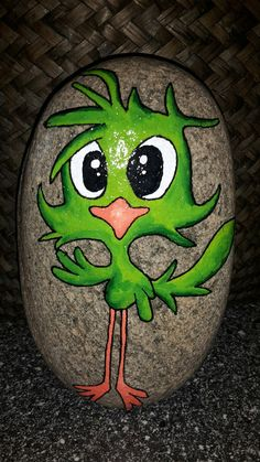 Cute green silly bird painted on a rock. Cute rock painting.