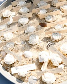 Round trays filled with sand and seashells corral escort cards together for an outdoor reception.