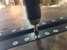 That is how it is done: those fittings are milled into the bottomside of the tabletop and attached with two rows of screws. Their purpose is to hold the glass elements, that serve as feet of the table. This is our own patented system, with with the table can be set up in a matter of just a few minutes.  #stammdesign #live #edge #wooden #slab #epoxytable #resintable #table #system #design #diy #woodwork #tischler #screw #fittings #feet