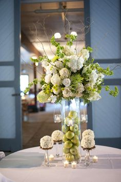 Apples, branches and flowers make an amazing tall wedding centerpiece
