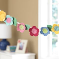 Love this pretty felt flower garden for adding a little extra fun and color to a girls bedroom or playroom. For more kids room decorating inspiration visit http://kidsroomdecorating.net