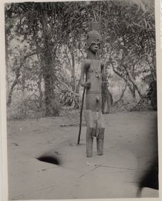 Nigeria, Ibo religious figure og Hrioku. Appears to represent adult [male?]. represented as wearing head-dress, scarification on face and torso. Dressed in real neck-ornament and loin-cloth. Medium: Gelatin silver print.