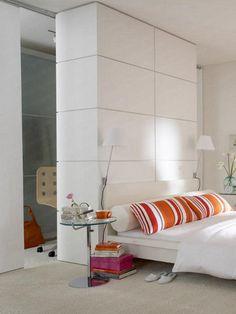 Deckenhoch abgeschirmt hinterm Bett: ein geräumiger Kleiderschrank und ein kleines Heimbüro mit zwei Arbeitsplätzen.Das Bett steht mitten