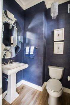 An oversized, sculptural mirror gives this powder room dimension beyond its small footprint. Textured wallpaper in a rich, dark gray lends the space a sophisticated air, while a petite chandelier adds sparkle.