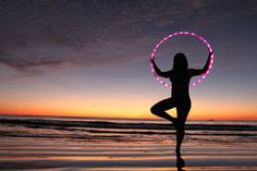 Gabbi Rose (CEO of Hoopnotica) hooping with an LED hoop on the beach at sunset in Costa Rica