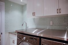 """We just had to go with the elongated glass tile. We considered a few other options, but the glass tile just had the shininess and coloration we wanted for the laundry room. We went with the 2""""x10"""" as it feels a bit more modern and the sizing worked out for us too. To make the modern glass feel more traditional, we installed it in a classic brick pattern."""