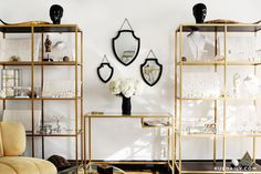 Zoe Chicco - Amazing living space features a pair of gold shelving units with glass shelves, Ikea VITTSJÖ Shelving Unit, filled with jewelry designed by Zoe Chicco flanking a gold console table with shelf situated under three staggered black shield mirrors.