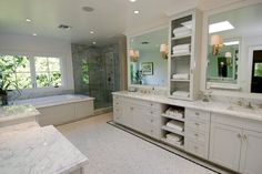 Spacious master bathroom features a single bathroom vanity painted light gray and adorned with glass knobs, divided into his and her sections, topped with white marble under white beveled mirrors illuminated by Longacre Sconces flanking open shelving.