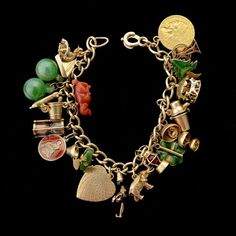 MULTI-STONE, ENAMEL, 14K YELLOW GOLD, STERLING SILVER, METAL CHARM BRACELET. The 14k yellow gold 6 1/2 inch open link bracelet featuring twenty-two charms as follows: A gold panner, a sailboat, two jade balls, an airplane, a champagne bucket, an hourglass, a coral dog, a sterling silver zodiac disc, a chalice, a frog, a heart figure, an elephant, a lantern, a four leaf clover, bells, a martini shaker, a merry-go-round, a tree, a ferris wheel and a U.S. 2 1/2 dollar Indian head coin.