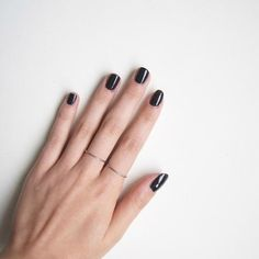 black manicure + thin silver rings.