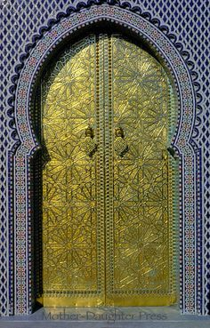 Islamic door carved in gold with surrounding mosaic tile.