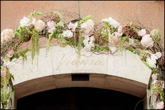 Archway with a loose, airy arrangement of blush florals with touches of green and white