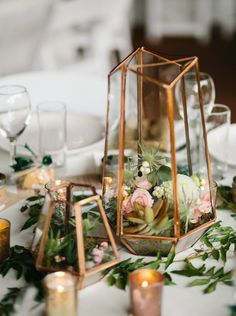 Terrarium centerpiece in mixed metallics with small floral and succulents / http://www.himisspuff.com/geometric-terrarium-wedding-ideas/