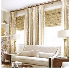 Large windows dressed with heavy khaki-and-cream striped draperies over bamboo blinds form a warm niche for the living room sofa. Layering window treatments adds interest to the room and gives multiple options for blocking light. Installing the curtain rod near the ceiling gives the illusion of higher ceilings.